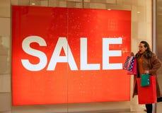 Verkoop glimlachende vrouw met het winkelen zakken Royalty-vrije Stock Afbeelding