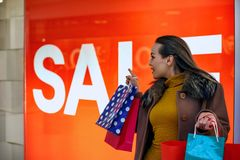 Verkoop: Het jonge en gelukkige vrouw winkelen Stock Afbeeldingen