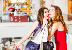 Verkoop, het winkelen en gelukkig mensenconcept - twee mooie vrouwen met het winkelen zakken geheime verrassingen Stock Foto's