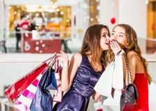 Verkoop, het winkelen en gelukkig mensenconcept - twee mooie vrouwen met het winkelen zakken geheime verrassingen Royalty-vrije Stock Foto