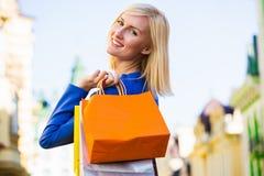 Verkoop, het winkelen, toerisme en gelukkig mensenconcept - mooie vrouw met het winkelen zakken in ctiy royalty-vrije stock afbeeldingen