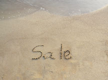 Verkoop in het zand wordt geschreven dat Stock Afbeeldingen