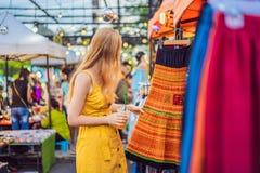 Verkoop, kleinhandels, het winkelen en kledingsconcept - de Vrouw kiest kleren in de Aziatische markt royalty-vrije stock foto's
