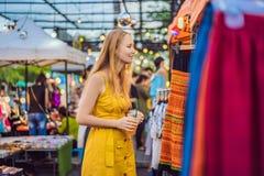 Verkoop, kleinhandels, het winkelen en kledingsconcept - de Vrouw kiest kleren in de Aziatische markt royalty-vrije stock afbeeldingen