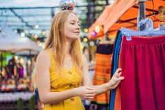 Verkoop, kleinhandels, het winkelen en kledingsconcept - de Vrouw kiest kleren in de Aziatische markt stock foto's