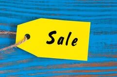 Verkoop, prijskaartje op blauwe houten achtergrond Stock Afbeelding