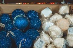 Verkoop van Kerstmisspeelgoed in de supermarkt Ballen van verschillende kleuren voor de Kerstboom op de supermarktplanken royalty-vrije stock afbeelding