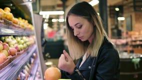 Verkoop, voedsel, het winkelen, consumentisme en mensenconcept Blondevrouw die de vruchten binnen kiezen van de kleurrijke planke stock videobeelden