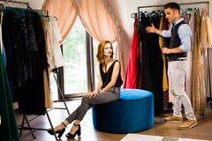 Verkoopadviseur die kleren voor de klant helpen te kiezen stock afbeelding