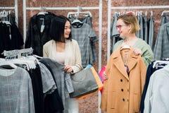 Verkoopadviseur het helpen kiest kleren voor de klant in de opslag Het winkelen met stilistconcept Vrouwelijke winkel stock foto