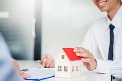 Verkoopagent die huis geven aan klant en tekenovereenkomstencontract, het concept van het Verzekeringshuis stock fotografie