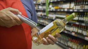 Verkoopbediende in rode de flessenstreepjescode van het aportaftasten bij wijnsectie in supermarkt stock footage