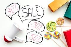 Verkoopconcept met megafoon Verklaar de verkoop Elektronische megafoon dichtbij woordverkoop in wolk, giftdozen en snoepjes  royalty-vrije stock fotografie