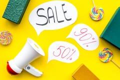 Verkoopconcept met megafoon Verklaar de verkoop Elektronische megafoon dichtbij woordverkoop in wolk, giftdozen en snoepjes  stock foto