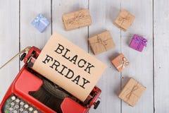 Verkoopconcept - schrijfmachine met ambachtdocument met tekst ' Zwarte friday' , giftdozen op witte houten achtergrond royalty-vrije stock afbeelding