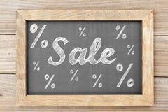Verkoopkrijt die met percentagetekens schrijven op bord Stock Afbeelding