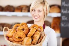 Verkoopster in bakkerij die diverse broodbroden toont stock afbeeldingen