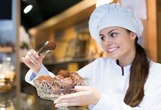 Verkoopster die brood en verschillend gebakje voor verkoop aanbieden royalty-vrije stock fotografie