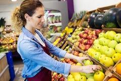 Verkoopster die vers fruit selecteren en voor werkdag in fruitshop voorbereidingen treffen Stock Afbeelding