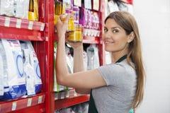 Verkoopster Holding Food Cans door Planken in Huisdierenopslag Stock Foto