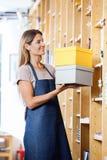 Verkoopster Keeping Cardboard Boxes in Planken stock fotografie