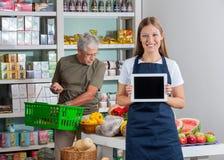 Verkoopster Showing Digital Tablet terwijl Hogere Mens Stock Foto