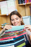 Verkoopster Stacking Colorful Papers in Winkel royalty-vrije stock fotografie