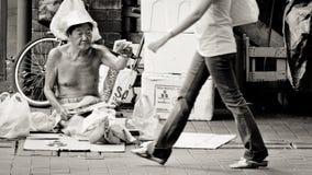 Verkoopt de armoede oude mens papieren zakdoekjepakken op de straat van Bugis, Singapore stock foto