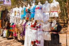 Verkopend traditionele Mexicaanse kleren met bloemendieborduurwerk en t-shirts met schedel op de straatmarkt wordt geschilderd in stock afbeelding