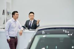 Verkoper die auto's tonen aan klant royalty-vrije stock afbeelding