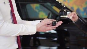 Verkoper die autosleutel geven aan klant binnen voorraad De autohandelaar geeft autosleutels aan een vrouw stock videobeelden