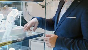 Verkoper die blauwe reeks in de winkel dragen stock fotografie
