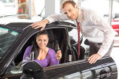 Verkoper die een auto verkopen aan gelukkige klant stock afbeeldingen