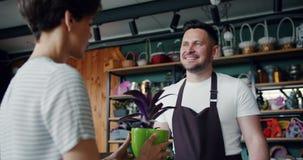 Verkoper die groene installatie verkopen aan mooi meisje in bloemwinkel die gevend pot spreken stock videobeelden