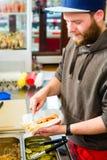 Verkoper die hotdog in snel voedselsnackbar maken stock afbeelding