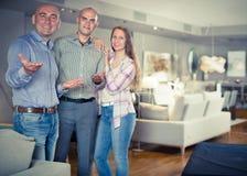 Verkoper die meubilair aanbieden aan familiepaar Royalty-vrije Stock Foto
