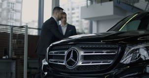 Verkoper die nieuwe auto voorstellen aan potentiële klant stock video