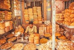 Verkoper die van suikergoed, snoepjes en cakes in een kleurrijke Indische markt zitten Stock Foto