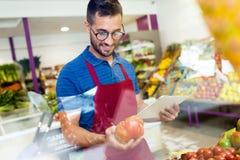 Verkoper die verse tomaten selecteren en voor werkdag in fruitshop voorbereidingen treffen Stock Afbeeldingen