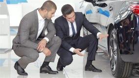 Verkoper en klant in het autohandel drijven stock footage