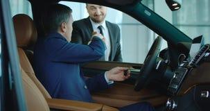 Verkoper het schudden hand aan koper binnen nieuwe auto stock foto