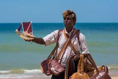 Verkoper op het strand dat met de hand gemaakte herinnerings varende boot verkoopt in Negombo royalty-vrije stock afbeeldingen