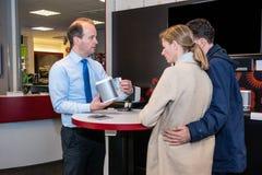 Verkoper Showing Compact Speaker aan Paar in Winkel royalty-vrije stock foto's