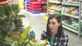 Verkoper van het portret de mooie meisje in een schort die met tuininstallaties werken stock footage