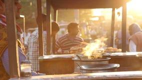 Verkopers die lokaal Indisch voedsel voorbereiden bij markttribunes in Jodhpur stock footage