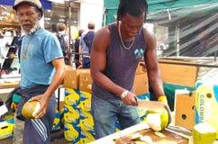 Verkopers verdelende kokosnoten bij een vlooienmarkt stock foto