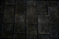 Verkratzte graue quadratische Straße deckt Beschaffenheit mit Ziegeln Stockfotos