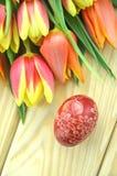 Verkratztes handgemachtes Osterei und Tulpen Lizenzfreies Stockbild