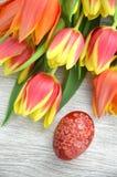 Verkratztes handgemachtes Osterei und Tulpen Lizenzfreie Stockbilder