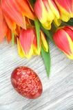 Verkratztes handgemachtes Osterei und Tulpen Stockfoto